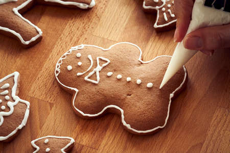 Decorating homemade gingerbread Christmas cookies with white icing - preparation of traditional pastry for the holidays Archivio Fotografico