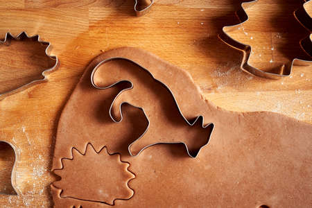 Cutting out animal shapes from rolled out dough to prepare gingerbread Christmas cookies, top view Archivio Fotografico