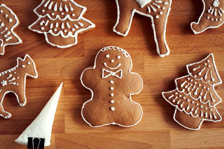 Decorating homemade gingerbread Christmas cookies with white icing using a cone, top view Archivio Fotografico