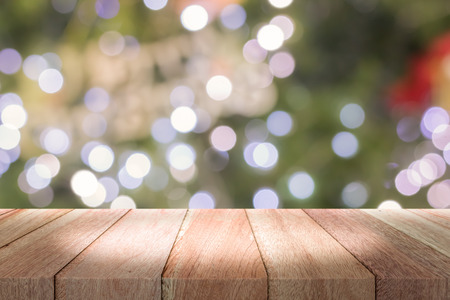 Empty wooden deck table with a sparkling bokeh of party lights in the background Stock Photo
