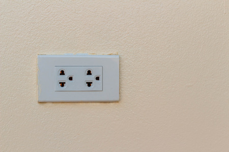 electric socket: White electric socket on the wall. Close up.