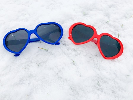 two Heart Shaped sun glasses bright blue and red on snow background winter valentines wedding love