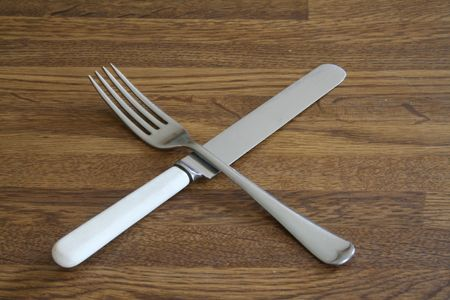 Knife and fork crossed on a wooden surface photo