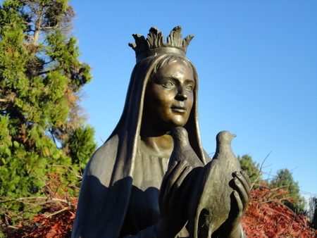 Bronze sculpture of a lady. She holds two doves on floreal and celestial background Stock Photo