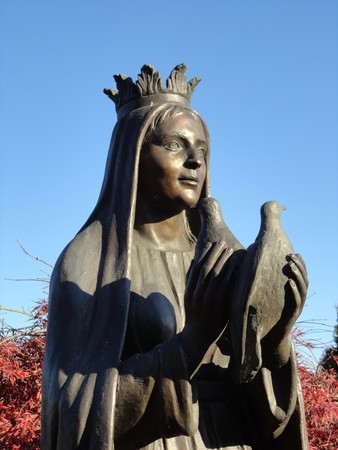queen of angels: Bronze sculpture of a queen. She holds two doves on celestial background