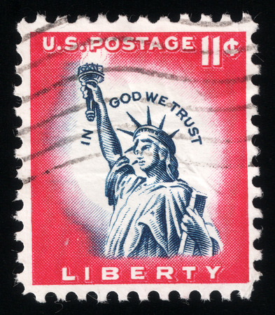 in god we trust: Post stamp printed in USA in 1961 shows a picture of Statue of Liberty in a close-up containing the motto: in god we trust Stock Photo