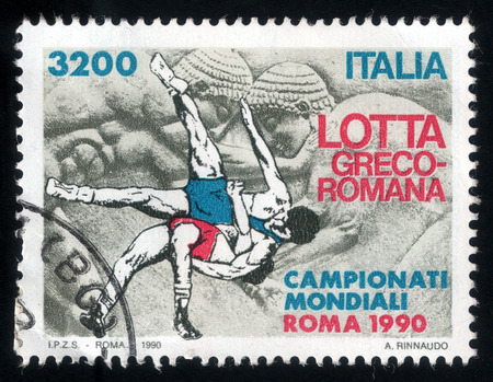 greco roman  roman: Postage stamp printed in Italy shows picture of Greco-Roman wrestling during international championship, 1990