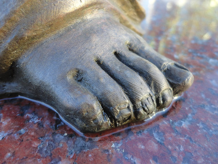 silver plated: Foot of an angel. Details of a sculpture placed on granite slab.