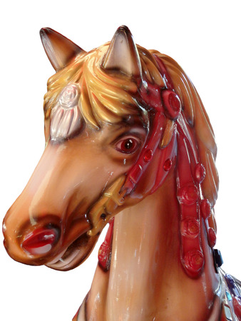 bridle: Head of a horse in a red bridle on a merry-go-round or carousel in a fairground or amusement park for children on an isolated background