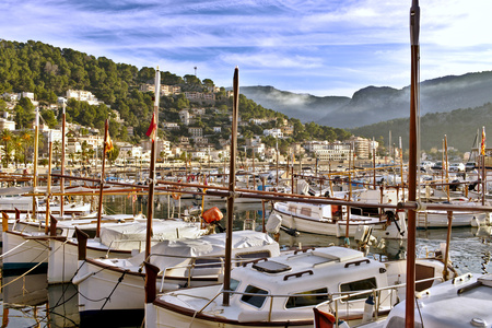Boats in Soller port with beautiful blue sky and misty hills, mallorca, spain.