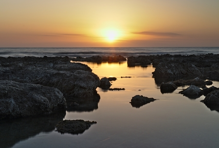 Sunrise over mediterranean sea with beautiful sky and rocky pools reflecting suns rays in foreground, cala, bona, mallorca, spain. 写真素材