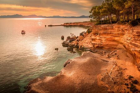 Betlem, near Colonia De Sant Pere. Cove, inlet, with old stone pier in distance. Boat or yacht anchored offshore on mediterranean sea captured in golden sunlight just before sunset. Small beach and wood in foreground. Mallorca, Spain.