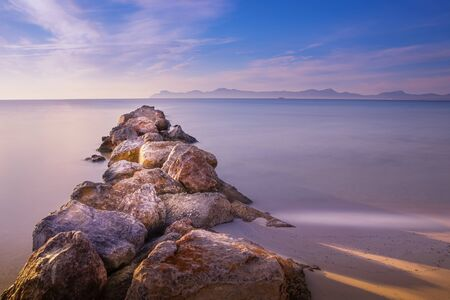 Pierjetty of rock and stone, playa de muro, alcudia, mallorca, spain, sunrise over mountains, beautiful smooth sea.