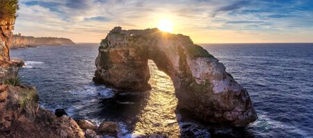 Natural arch in the mediterranean sea, sunrise with golden sunbeam and beautiful colourful sky, Santanyi, Mallorca, Spain.