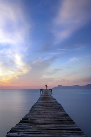 Lone person standing at end of wooden boardwalk at sunrise, with calm sea and beautiful colourful sky and mountains in the distance, Alcudia beach, Mallorca, Spain.
