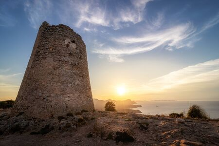 Son Jaumell watchtower at sunset with sun flare, located between Cala Agulla and Cala Mesquida, Mallorca, Spain.