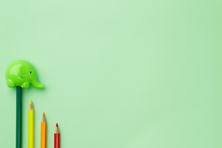 childish pencil sharpener in the form of an elephant and four pencils stairs down on a pale green background
