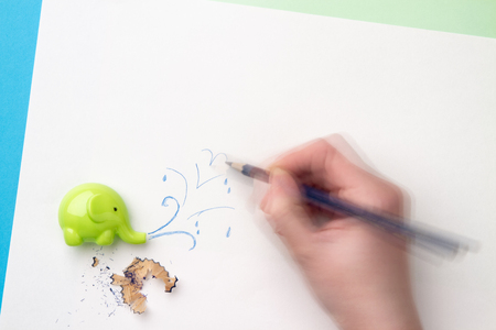 Dynamic hand drawing water splashes from the sharpener in the form of an elephant