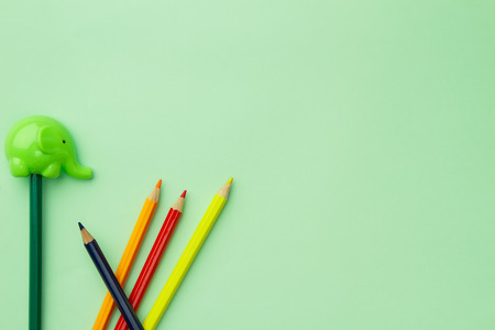 Light green pencil sharpener in the form of an elephant and five chaotic pencils on a pale green background Banco de Imagens