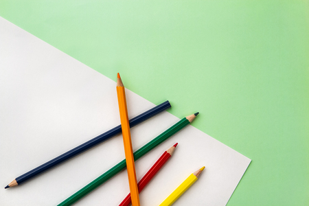 white sheet of paper and five pencils on a pea green color paper background. Copyspace Banco de Imagens