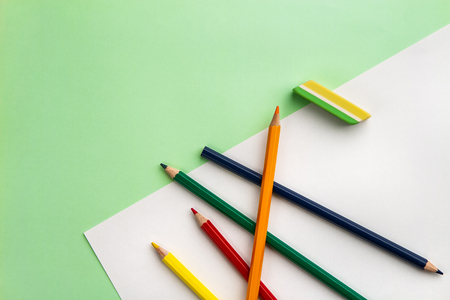 white sheet of paper, five pencils and an eraser on a light green paper background. Copyspace