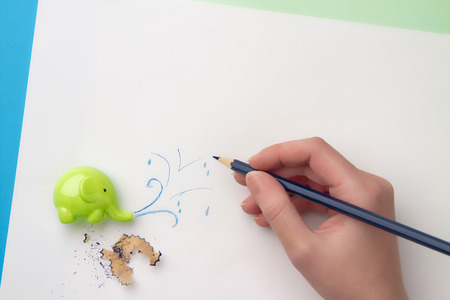 Ð¡ute childrens sharpener in the form of an elephant, hand with blue pencil drawing a spray of water and a pencil filings. Flat lay Banco de Imagens
