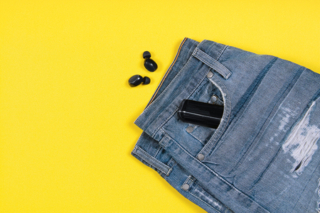 Flat lay composition with wireless earbuds, jeans and charging case in its pocket on yellow background with copy space