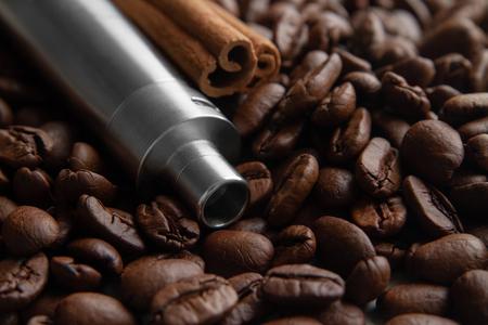 Coffee beans, E-cigarette and canella . Coffee and cinnamon flavored vape juice concept Banco de Imagens