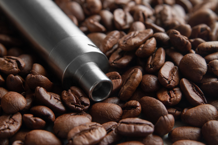 Coffee Flavor E-Juice concept. Handheld vape device on the background of Soft focused coffee beans