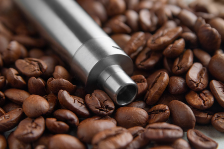 Stainless steel Vape device mod lies on the background of coffee beans