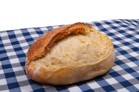 Artisan traditional french bread lies on table covered with rustic style checkered blue white tablecloth Banco de Imagens