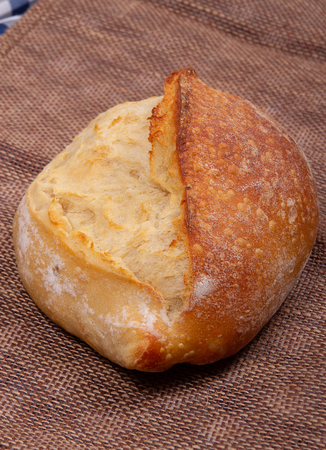 edge view of a loaf of bread with ruddy crust on sacking background