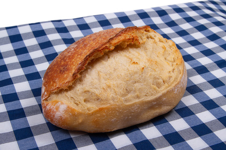 whole Loaf of homemade white bread on rustic blue white textile background
