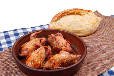 Roasted pigeon in clay pot and loaf of white bread lie on rustic table with white copy space background on top