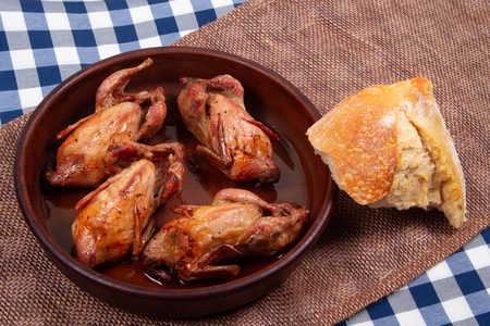 Roasted quail and Chunk of white bread. Rustic style.