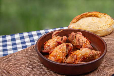 Roasted quail in clay pan and French white bread lie on the table outdoor Imagens