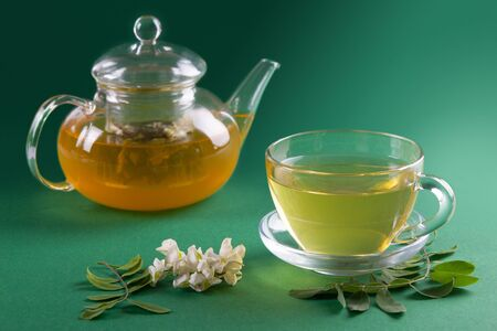 Flowers of acacia and Acacia tea in transparent tea pot and cup on green plain background