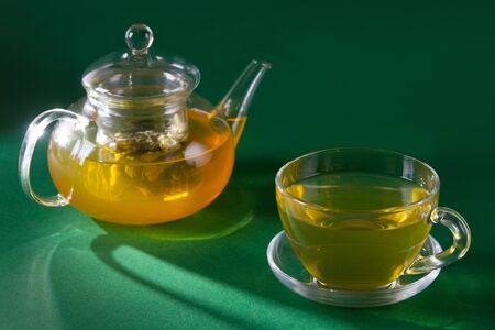 Glass tea cup and tea pot on green background with hard shadows. Side view. Soft focus