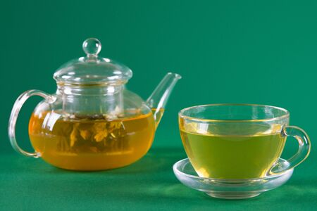 Glass tea cup and tea pot on green background. Side view. Soft focus