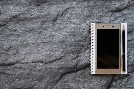 smartphone notebook and paper wordpad on stone background