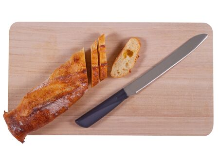 Wooden cutting board with sliced baguette and knife isolated on white background 写真素材