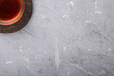 Rough plaster background with chinese tea cup and pu erh tea at upper left corner