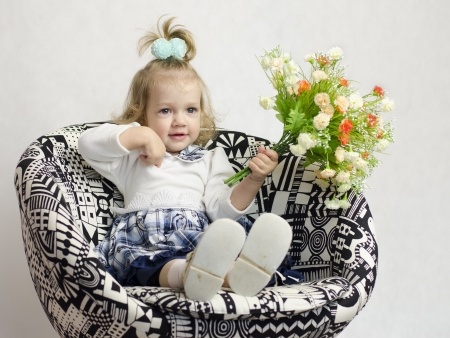 A little girl sat on a chair with a bouquet of flowers photo
