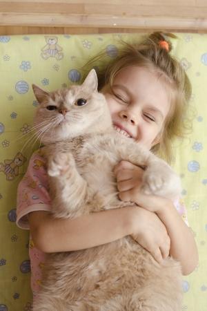 The little girl hugging the cat lying on a mattress on the floor Foto de archivo