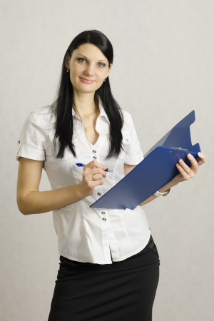 Business girl listens and makes notes in a folder photo
