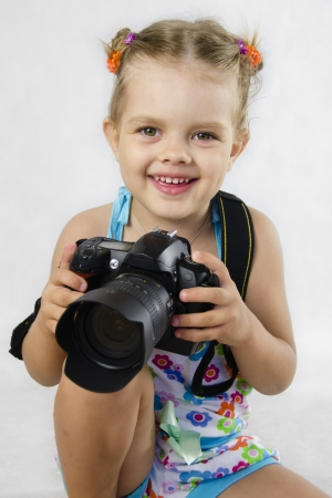 fas: A merry girl hold SLR camera Stock Photo