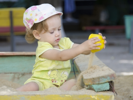 Little girl playing in the sandbox photo