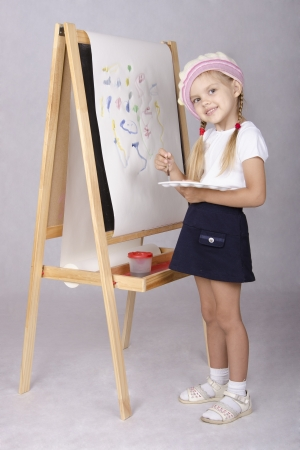 The girl in the image of the artist draws on the easel photo