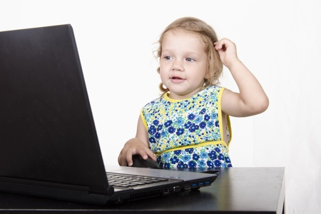 consistently: The girl sitting at the table and running laptop Stock Photo