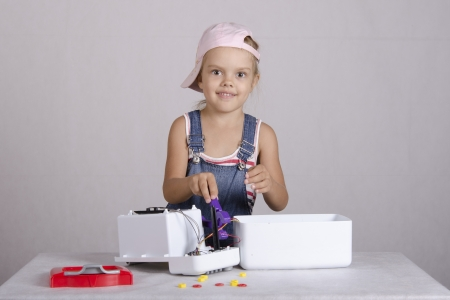 Girl repairs toy microwave photo
